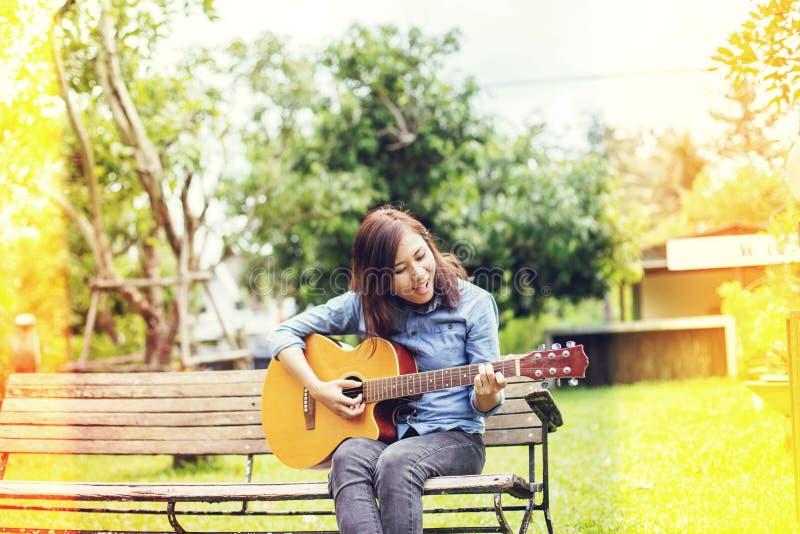 Schließen Sie oben vom jungen Hippie, den Frau Gitarre im Park übte, glücklich und genießen Sie, Gitarre zu spielen stockfotografie