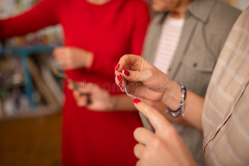 Schließen Sie oben vom jungen Künstler mit den roten Nägeln, die malende Palette halten lizenzfreie stockfotografie