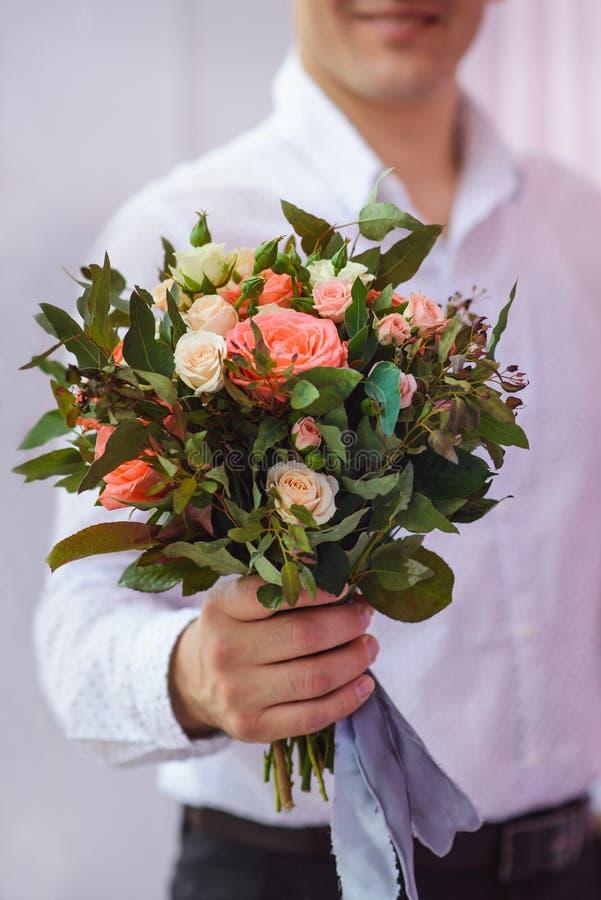 Schließen Sie oben vom jungen Mann im weißen Hemd, das Blumenstrauß von Blumen als Überraschung, Fokus auf Rosen gibt lizenzfreies stockfoto