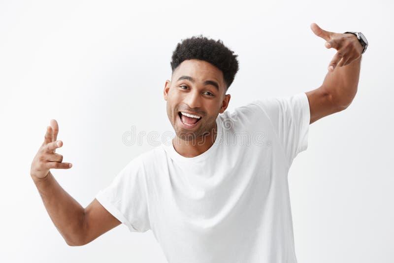 Schließen Sie oben vom jungen netten dunkelhäutigen schönen afrikanischen Mann mit dem gelockten Haar im weißen T-Shirt lachend u stockbilder