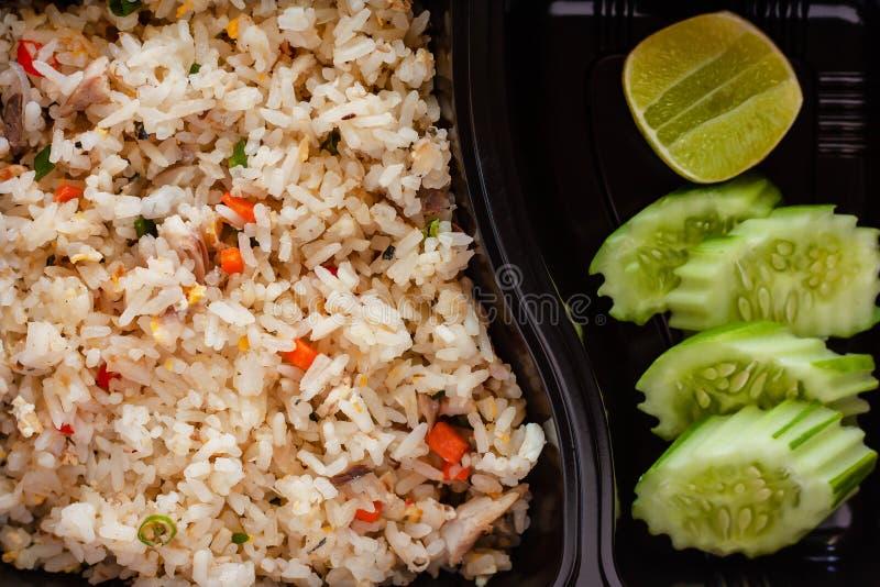 Schließen Sie oben vom köstlichen gebratenen Reis mit Gurke und Zitrone auf Seite in der Brotdose stockbilder
