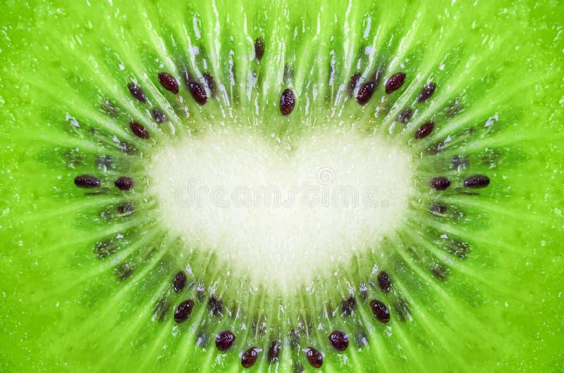 Schließen Sie oben vom Kiwibeschaffenheitshintergrund mit Herzform lizenzfreies stockbild