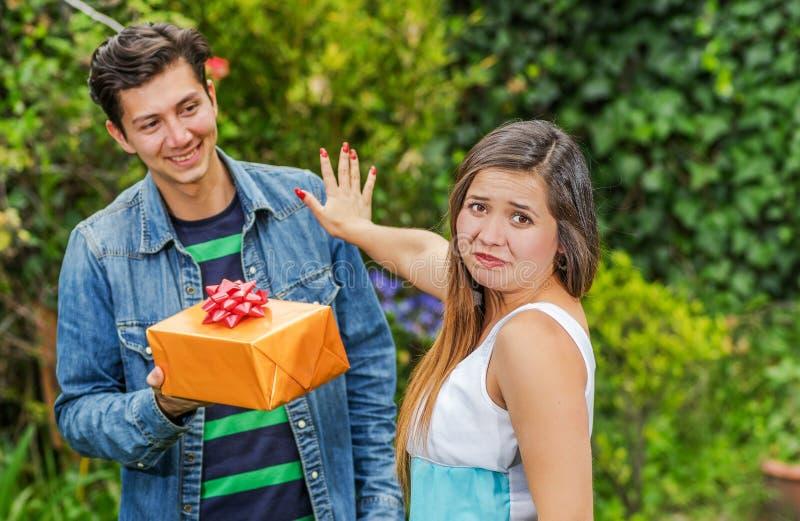 Schließen Sie oben vom lächelnden Mann, der ein Geschenk und seine Freundin hält und ihren Arm ausdehnen ihn ignorierend, Freundz stockbild