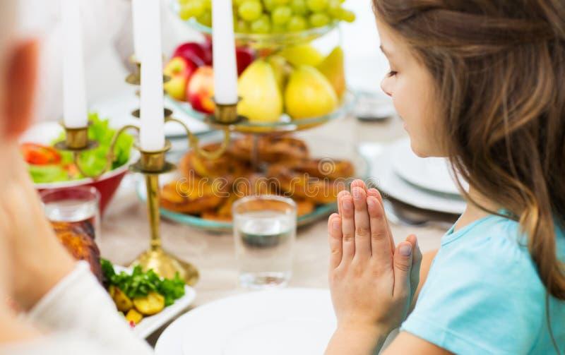 Schließen Sie oben vom Mädchen, das am Feiertagsabendessen betet lizenzfreie stockfotos