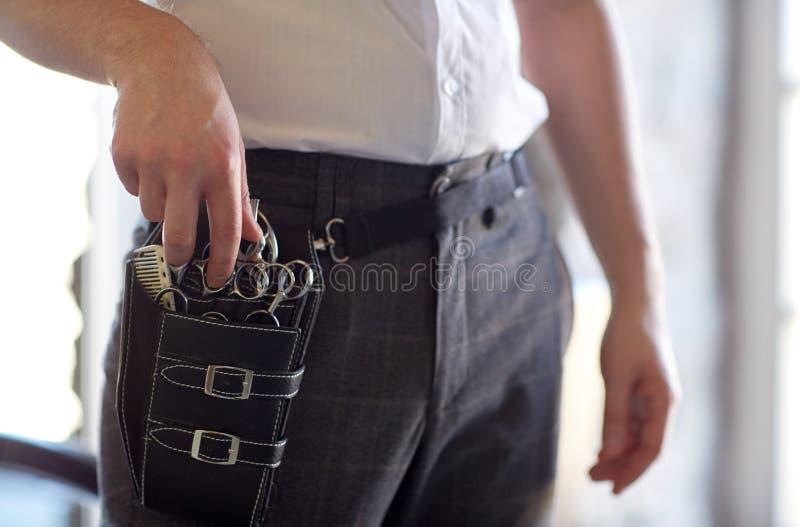 Schließen Sie oben vom männlichen Stilisten mit Werkzeugkasten am Salon stockfoto
