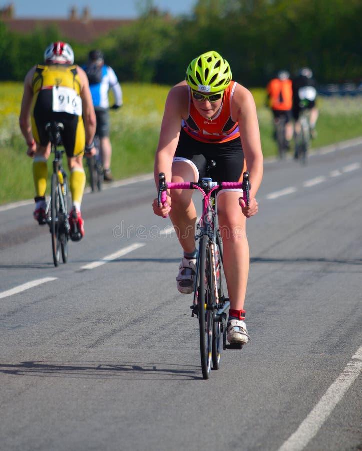 Schließen Sie oben vom männlichen triathlete auf Radfahrenstadium der Straße stockfotos