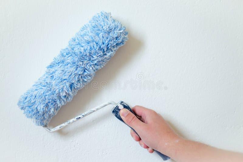 Schließen Sie oben vom Malerarm, der eine Wand mit Farbenrolle malt Berufsarbeiter-Hand, die schmutzige Farbenrolle hält stockfotografie