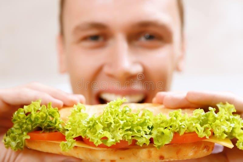 Schließen Sie oben vom Mann, der Bisssandwich nimmt stockbild