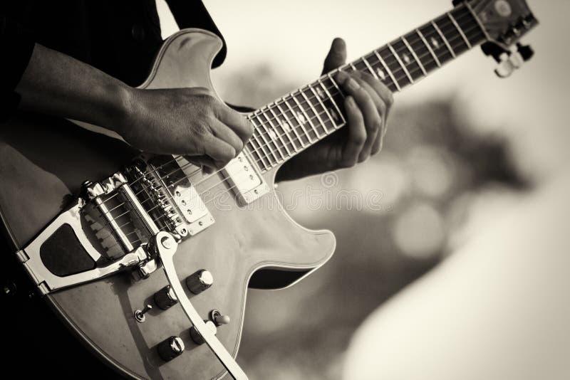 Schließen Sie oben vom Mann, der eine Gitarre spielt stockfotos