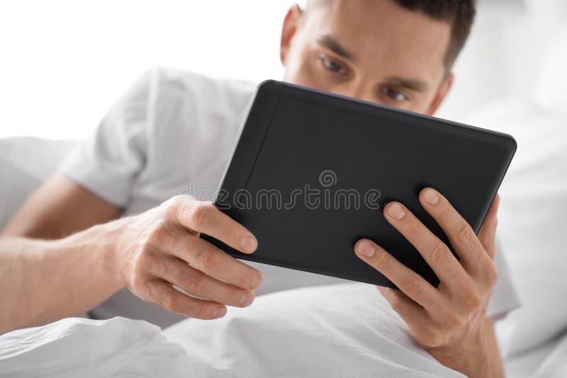 Schließen Sie oben vom Mann mit Tablet-Computer im Bett lizenzfreie stockfotografie