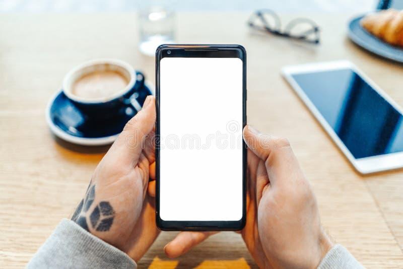 Schließen Sie oben vom Mann tätowierte die Hände, die Handy mit leerem Bildschirm halten lizenzfreie stockbilder