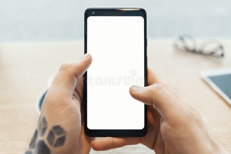 Schließen Sie oben vom Mann tätowierte die Hände, die Handy mit leerem Bildschirm halten lizenzfreie stockfotografie
