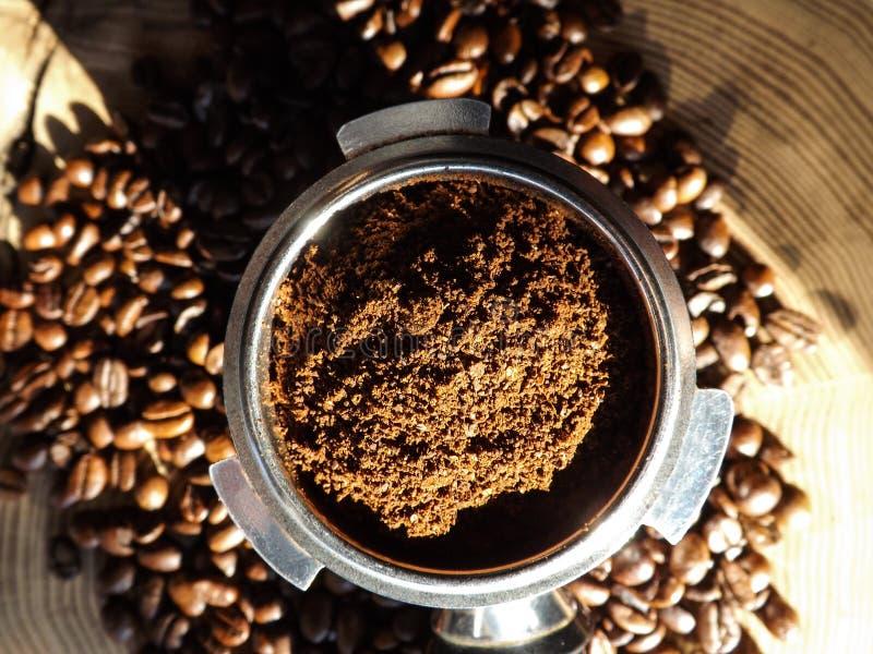 Schließen Sie oben vom Metall-portafilter, das mit Kaffeepulver und Kaffeebohnen herum auf Holztisch gefüllt wird lizenzfreie stockfotos