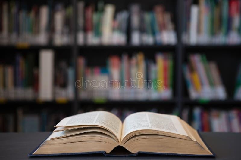 Schließen Sie oben vom offenen Buch auf Tabelle gegen Regal lizenzfreie stockfotos