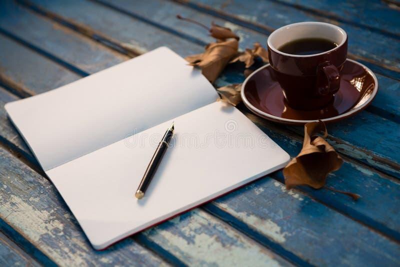 Schließen Sie oben vom offenen Buch durch Kaffeetasse stockfotografie