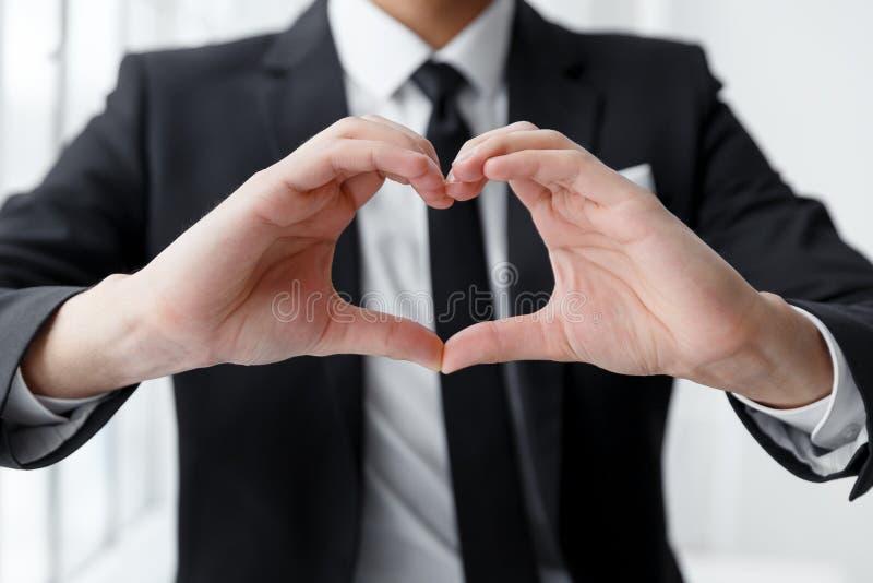 Schließen Sie oben vom Porträt des Geschäftsmannes ein Herz mit seinen Händen machend stockbilder