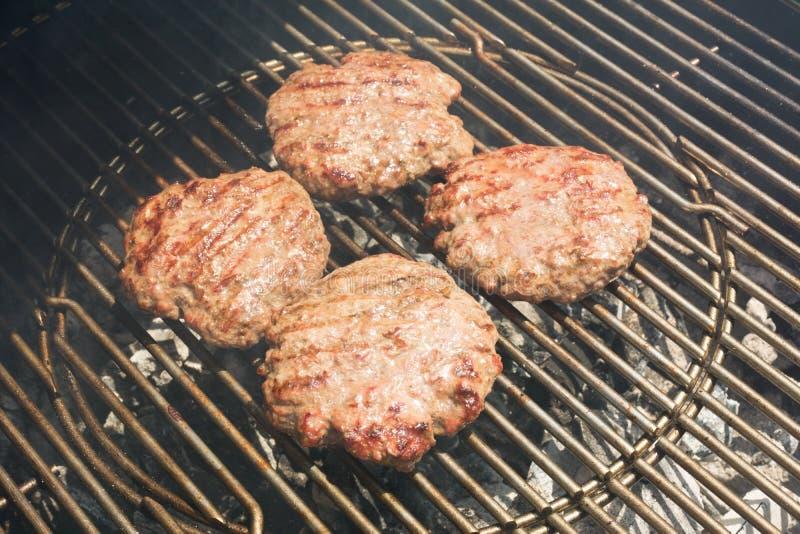 Schließen Sie oben vom Rindfleisch-Hamburger, der auf einem Holzkohlen-Grill kocht lizenzfreie stockfotografie