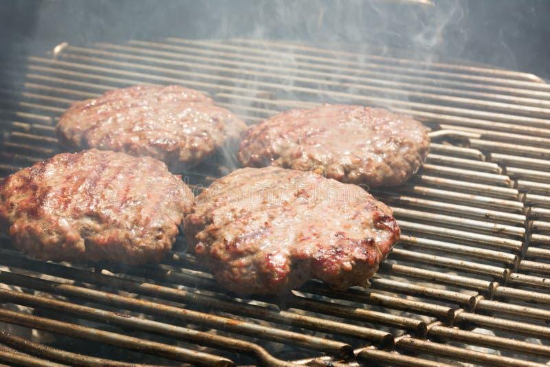 Schließen Sie oben vom Rindfleisch-Hamburger, der auf einem Holzkohlen-Grill kocht stockfoto