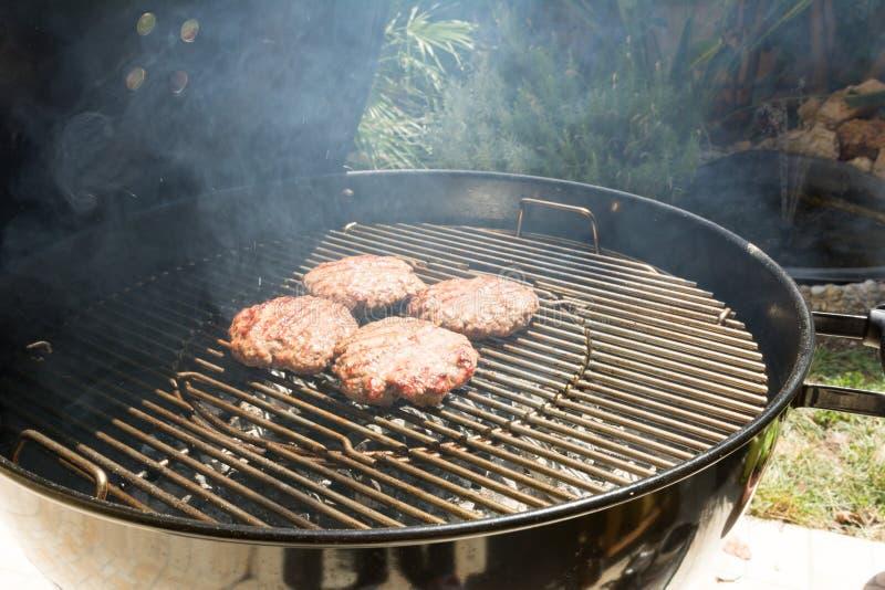 Schließen Sie oben vom Rindfleisch-Hamburger, der auf einem Holzkohlen-Grill kocht lizenzfreies stockfoto