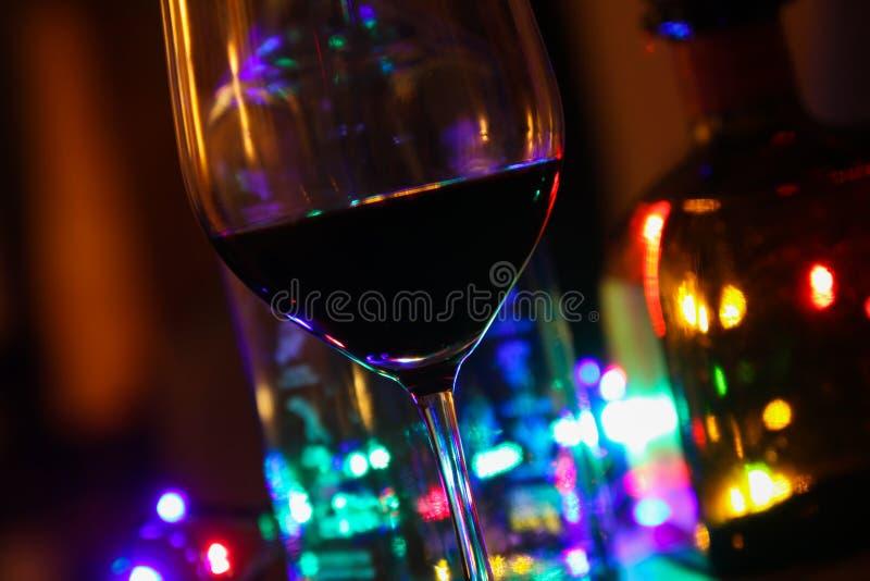 Schließen Sie oben vom Rotweinglas mit Flaschen Alkohol und buntem elektrischem Licht lizenzfreies stockfoto