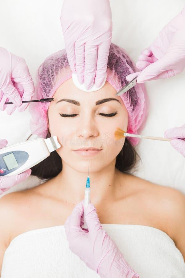 Schließen Sie oben vom schönen Gesicht einer jungen Frau Viele Hände, die Cosmetologywerkzeuge nahe Gesichtspatienten halten stockfoto