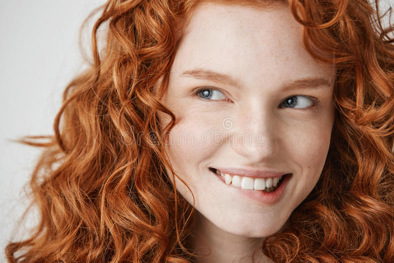 Schließen Sie oben vom schönen Mädchen mit dem gelockten roten Haar und der lächelnden beißenden Lippe der Sommersprossen über we lizenzfreie stockfotografie