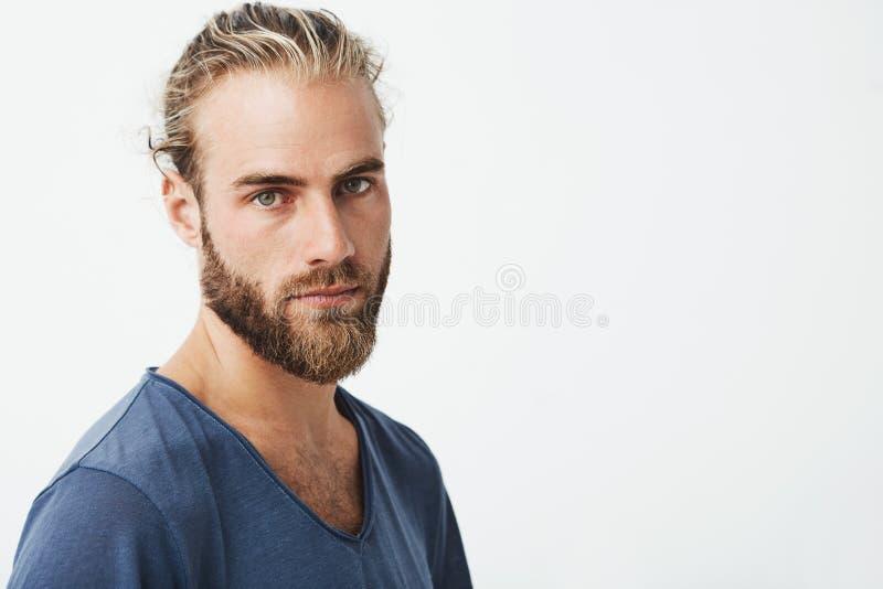 Schließen Sie oben vom schönen schwedischen Mann mit stilvoller Frisur und vom Bart im blauen T-Shirt, das in camera mit ernstem  stockbild