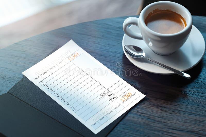 Schlie?en Sie oben vom Scheck und von der Kaffeetasse auf Holztisch im modernen Caf? Wiedergabe 3d lizenzfreie abbildung