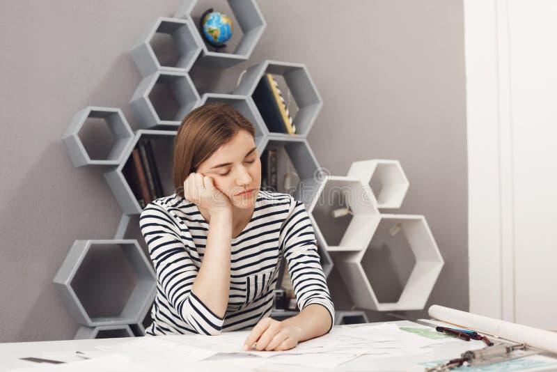 Schließen Sie oben vom schläfrigen jungen schönen weiblichen Manager mit dem dunklen Haar und gestreiften dem Hemd halten Haupt m stockfotos