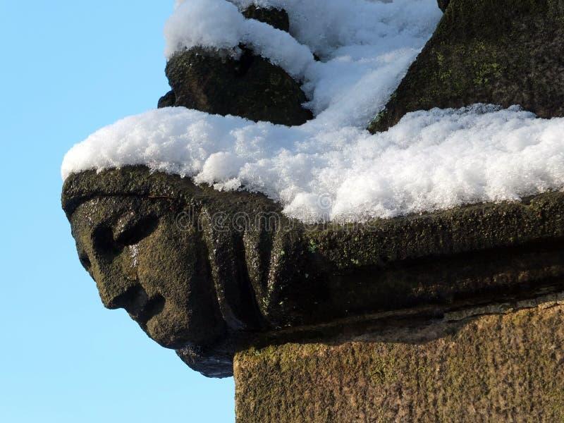 Schließen Sie oben vom Schnitzen des Gesichtes einer Frau im Profil auf der Ecke der alten ruinierten mittelalterlichen Kirche im stockbilder