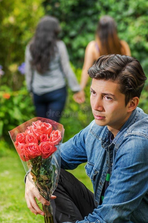 Schließen Sie oben vom traurigen Mann, der eine Baumwollstoffjacke und schwarzen Hosen sitzen in den haltenen Grundblumen in sein lizenzfreie stockfotos