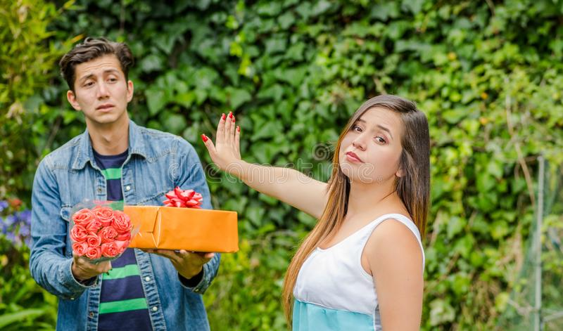Schließen Sie oben vom unscharfen Mann, der ein Geschenk hält und Blumen mit entsetztem Gesicht nach sehen seine Freundin, ihren  stockbild