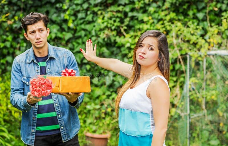 Schließen Sie oben vom unscharfen Mann, der ein Geschenk hält und Blumen mit traurigem Gesicht nach sehen seine Freundin, ihr Arm stockfotos