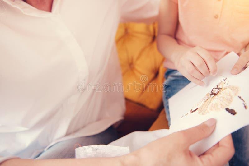 Schließen Sie oben vom versuchenden Sticken des Kleinkindes für erstes Mal stockfotos