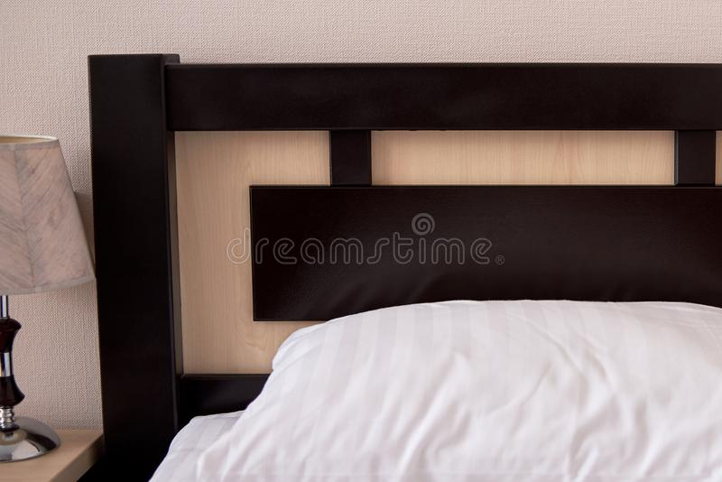 Schließen Sie oben vom weißen weichen Kissen auf Einzelbett mit brauner hölzerner Kopfende im Hotelschlafzimmerinnenraum, Kopienr lizenzfreie stockfotos