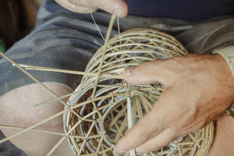 Schließen Sie oben vom Weiden-craftsman& x27; s-Hände, die in einem Korb arbeiten stockfoto