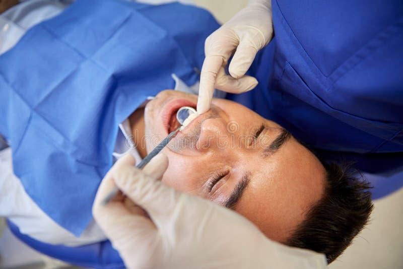 Schließen Sie oben vom Zahnarzt, der männliche geduldige Zähne überprüft stockfoto