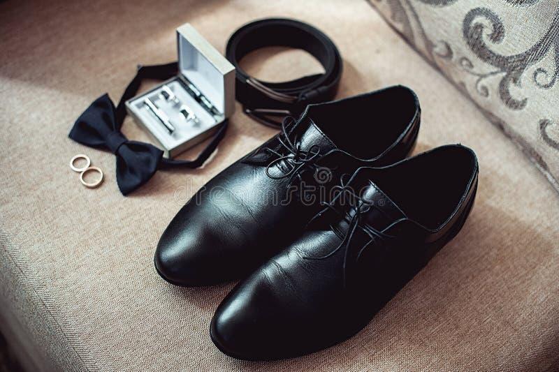 Schließen Sie oben vom Zubehör des modernen Mannes Eheringe, schwarzes bowtie, Lederschuhe, Gurt und Manschettenknöpfe lizenzfreies stockfoto