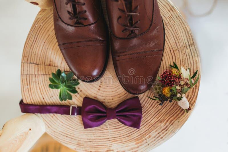 Schließen Sie oben vom Zubehör des modernen Mannes purpurroter Fliege, Lederschuhe, Gurt und Blume Boutonniere auf dem hölzernen  lizenzfreie stockfotografie