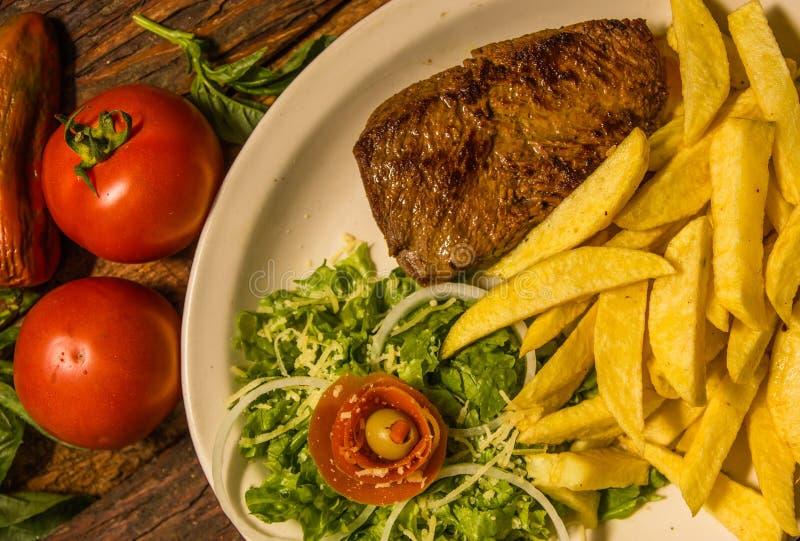 Schließen Sie oben von ausführlichem gegrilltem Rindfleischsteak mit Franzosen gebratener Kartoffel, die Tomate, an gedient in de stockfotos