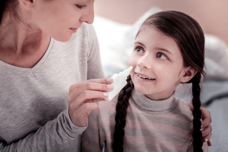 Schließen Sie oben von begeistertem Kind mit nasalen Tropfen lizenzfreie stockfotos
