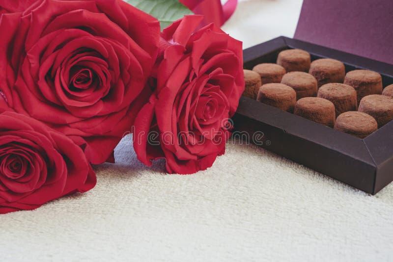 Schließen Sie oben von blühenden roten Rosen und vom eleganten Kasten Schokoladentrüffeln Valentinstag oder romantisches Feierkon stockfoto