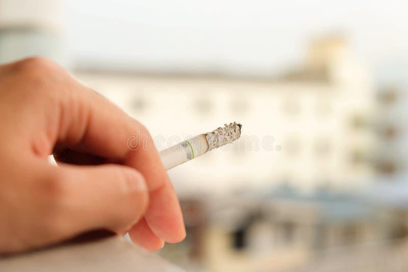 Schließen Sie oben von brennender Zigarette in der Hand und Zigarette rauchen Gesundes Konzept stockbild