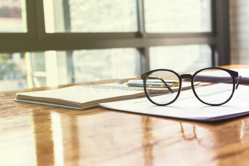 Schließen Sie oben von den Augengläsern auf Arbeitsschreibtisch mit Diagramm und Laptop lizenzfreie stockfotos