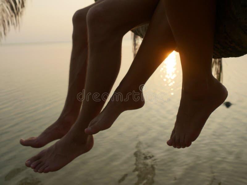 Schließen Sie oben von den Beinen eines Paares, das auf einer Palme während des Sonnenuntergangs auf der Küste sitzt stockfoto