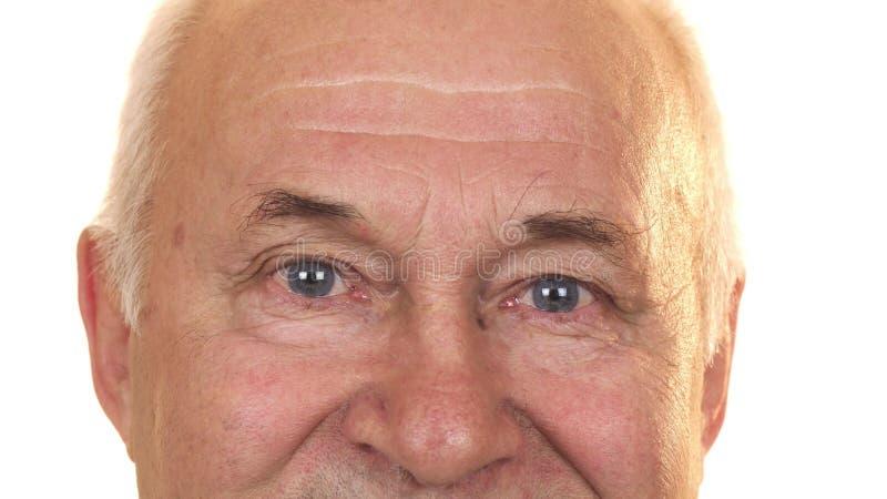 Schließen Sie oben von den blauen Augen eines netten älteren lokalisierten Mannes lizenzfreies stockfoto