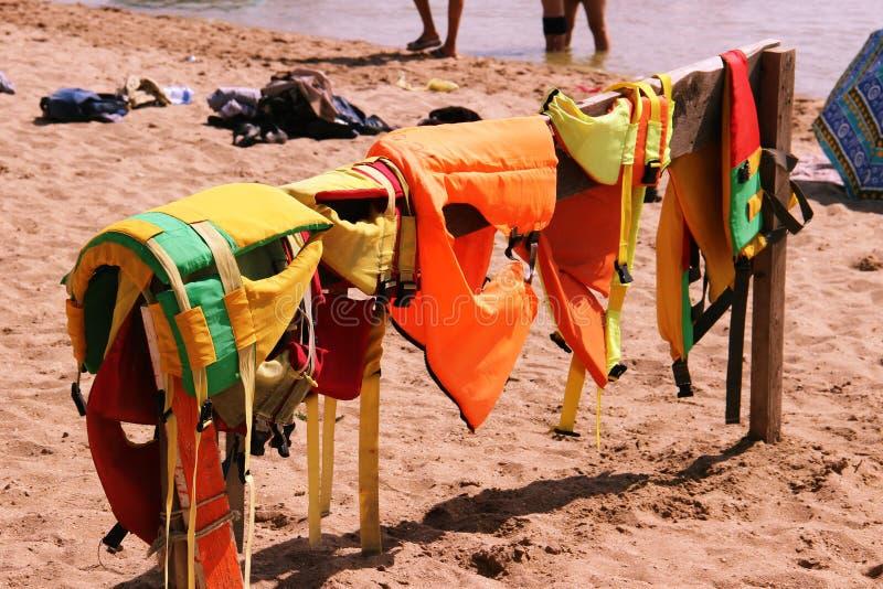 Schließen Sie oben von den bunten Schwimmwesten mit Meer und versanden Sie Hintergrund Ausrüstung zur Sicherheit im Wassertranspo stockbild