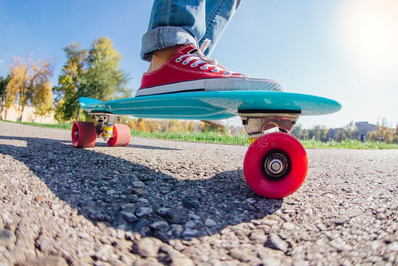 Schließen Sie oben von den Füßen auf blauem Plastikpennyrochenbrett mit rosa Rädern lizenzfreie stockbilder