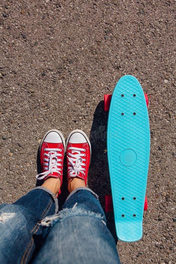 Schließen Sie oben von den Füßen auf blauem Plastikpennyrochenbrett mit rosa Rädern lizenzfreies stockbild
