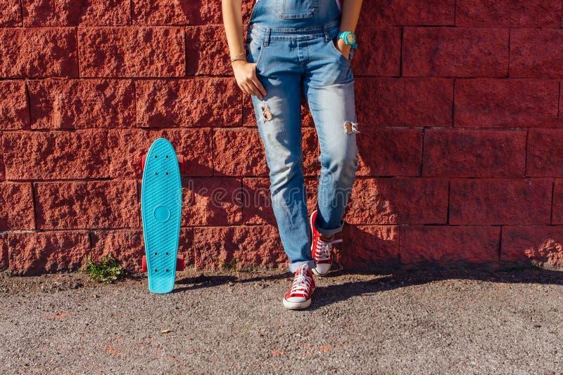 Schließen Sie oben von den Füßen und vom blauen Pennyrochenbrett mit rosa Rädern stockfotografie
